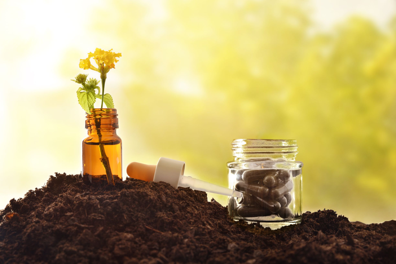 Envases cosméticos con una segunda vida. Una botellita cuentagotas reconvertida en jarrón con una flores amarillas en su interior, junto a un frasco de cristal reutilizado como pastillero con unas cápsulas en su interior.
