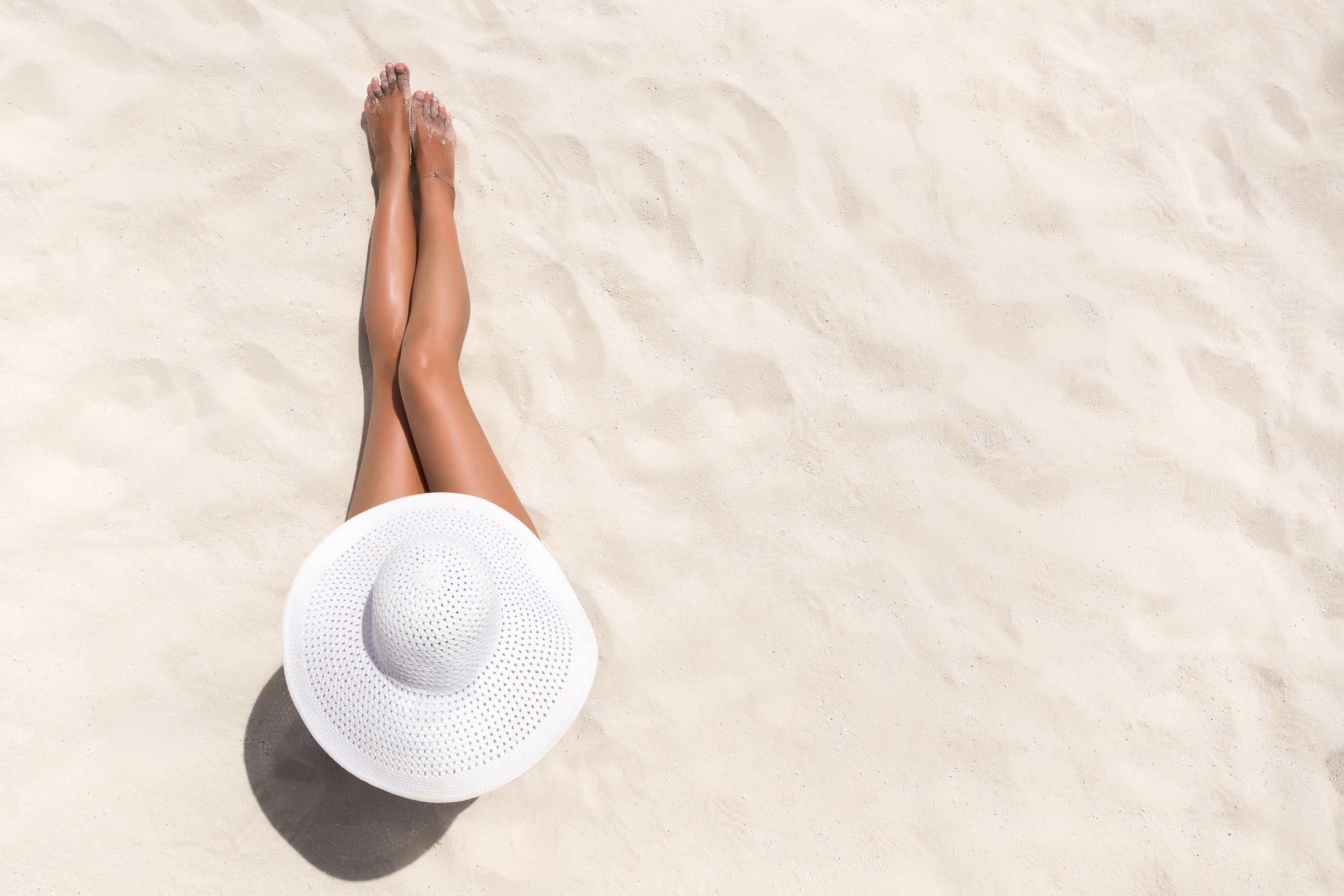 Sobre un fondo de arena de playa blanca vemos desde arriba una mujer tomando el sol. Destaca su sombrero blanco que le cubre rostro y torso y del que salen las piernas bronceadas.